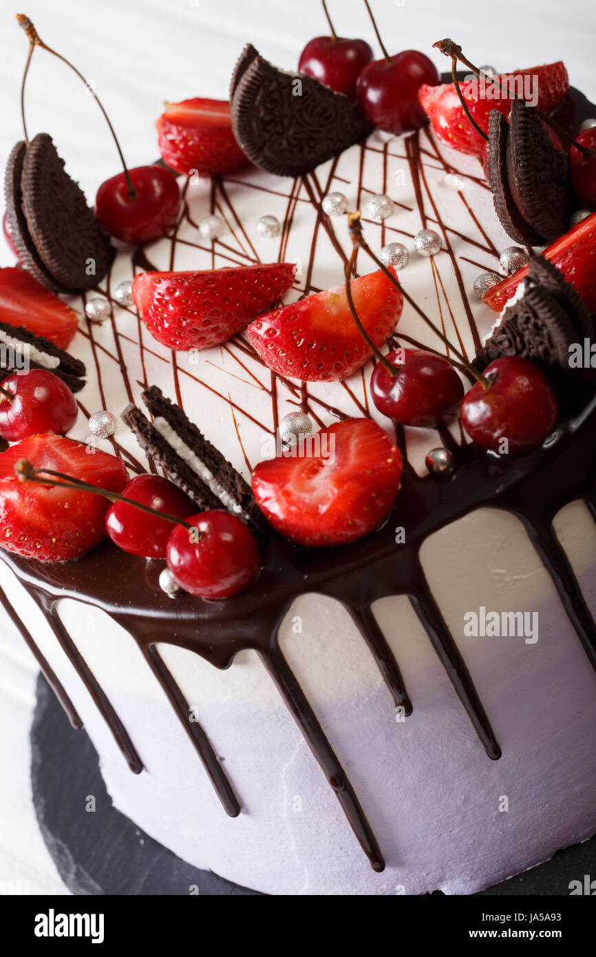 Delicate cheesecake with strawberry and cherry, decorated cookies and chocolate close-up on the table. vertical - Stock Image