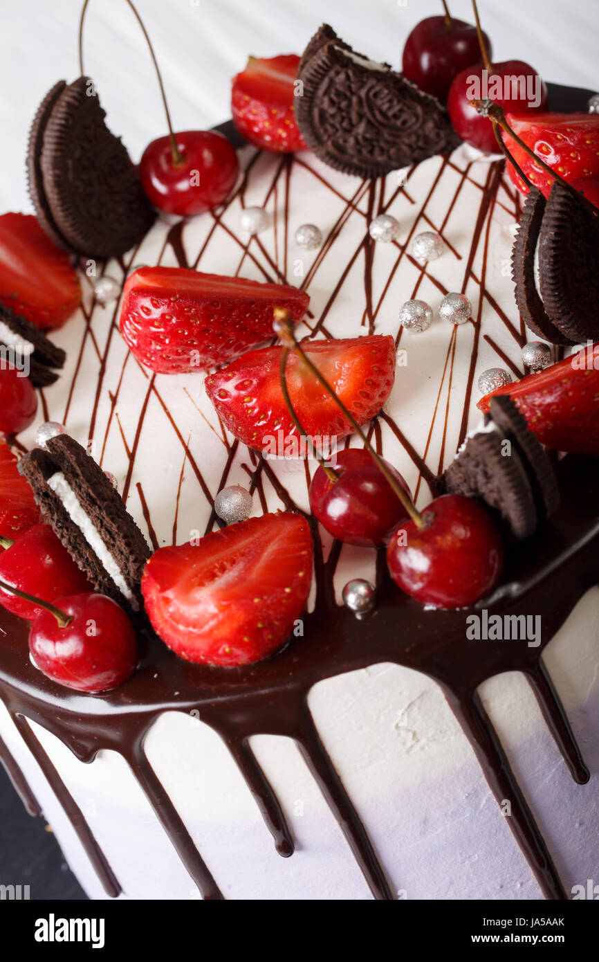 Mousse cake with fresh strawberries and cherries, decorated with biscuits and chocolate close-up. vertical - Stock Image