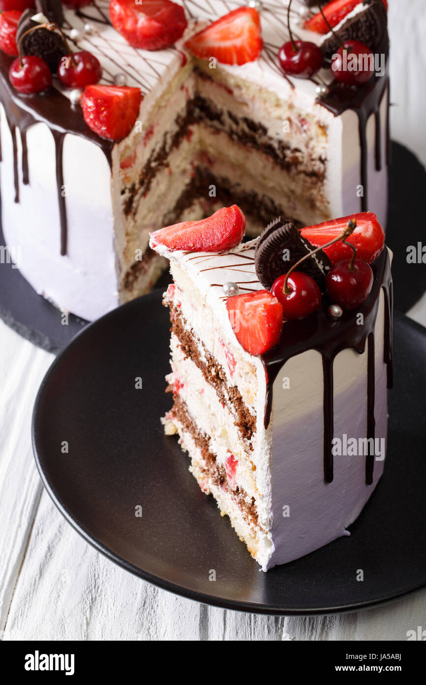 sliced mousse cake with fresh strawberry and cherry, decorated with chocolate closeup. vertical - Stock Image