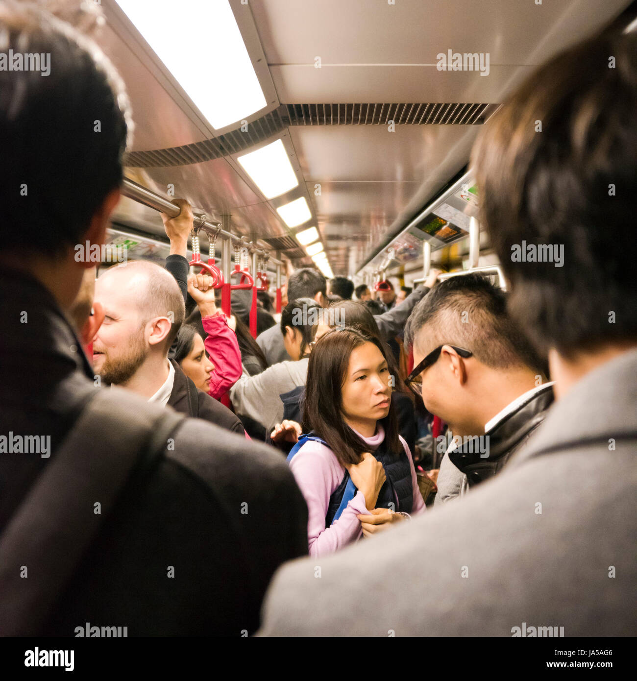 Square view of passengers inside the MTR, mass transit railway, in Hong Kong, China. - Stock Image