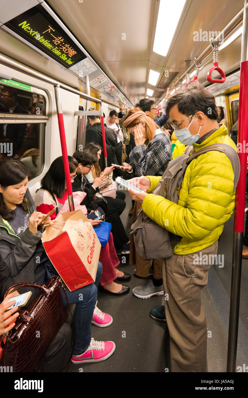 Vertical view of passengers inside the MTR, mass transit railway, in Hong Kong, China. - Stock Image