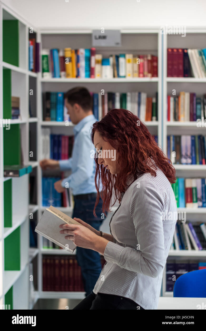 Beautiful redhead student girl holding book in the library with her back leaned toward bookshelf. Handsome guy research - Stock Image