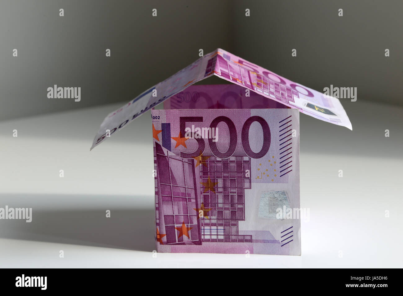 A house bulit from 500 Euro bills, symbol of building a house and paying mortgage Stock Photo