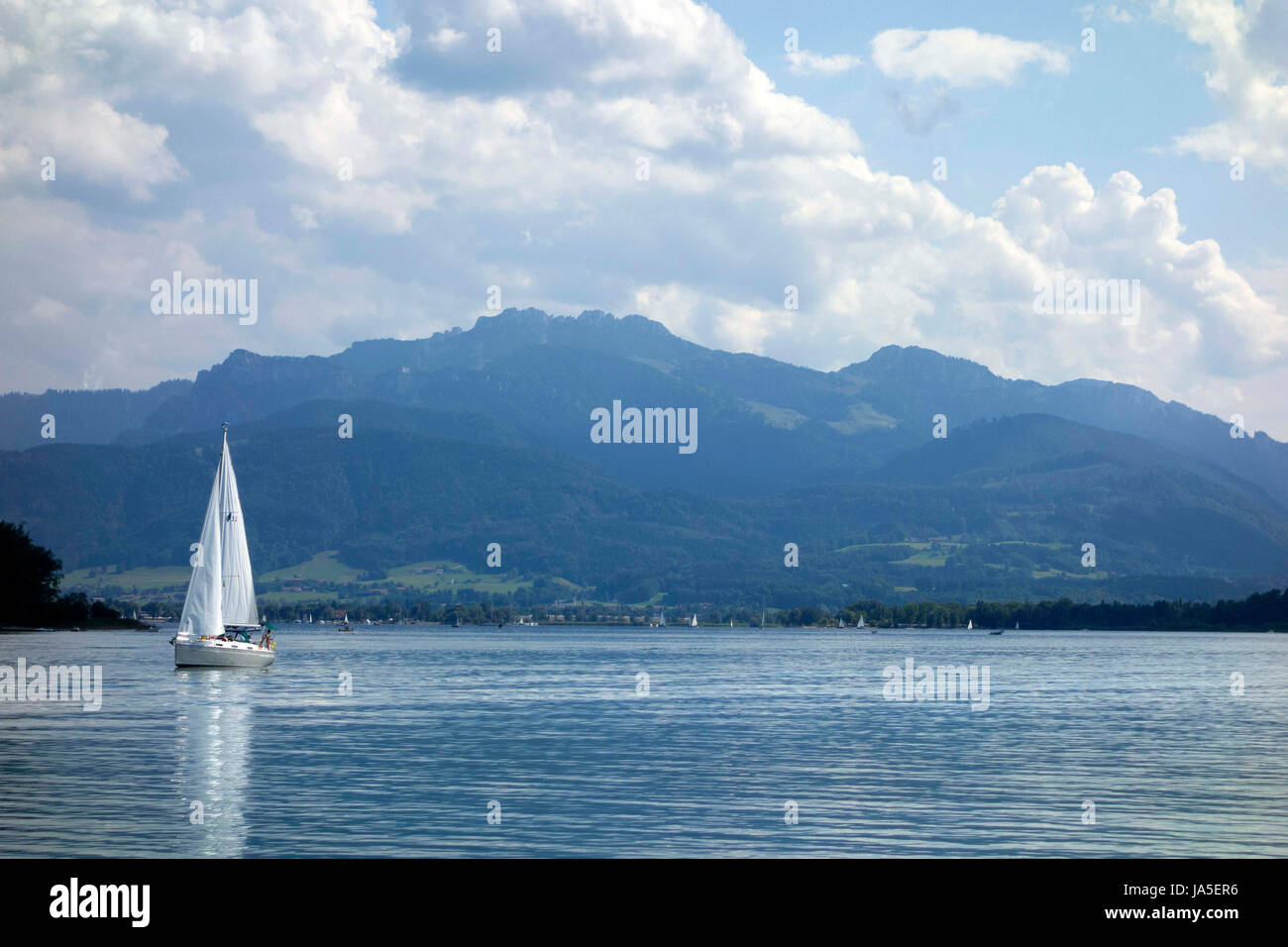 Small sail boat on lake,  with Bavarian alps in background, Chiemsee Upper Bavaria Germany Stock Photo