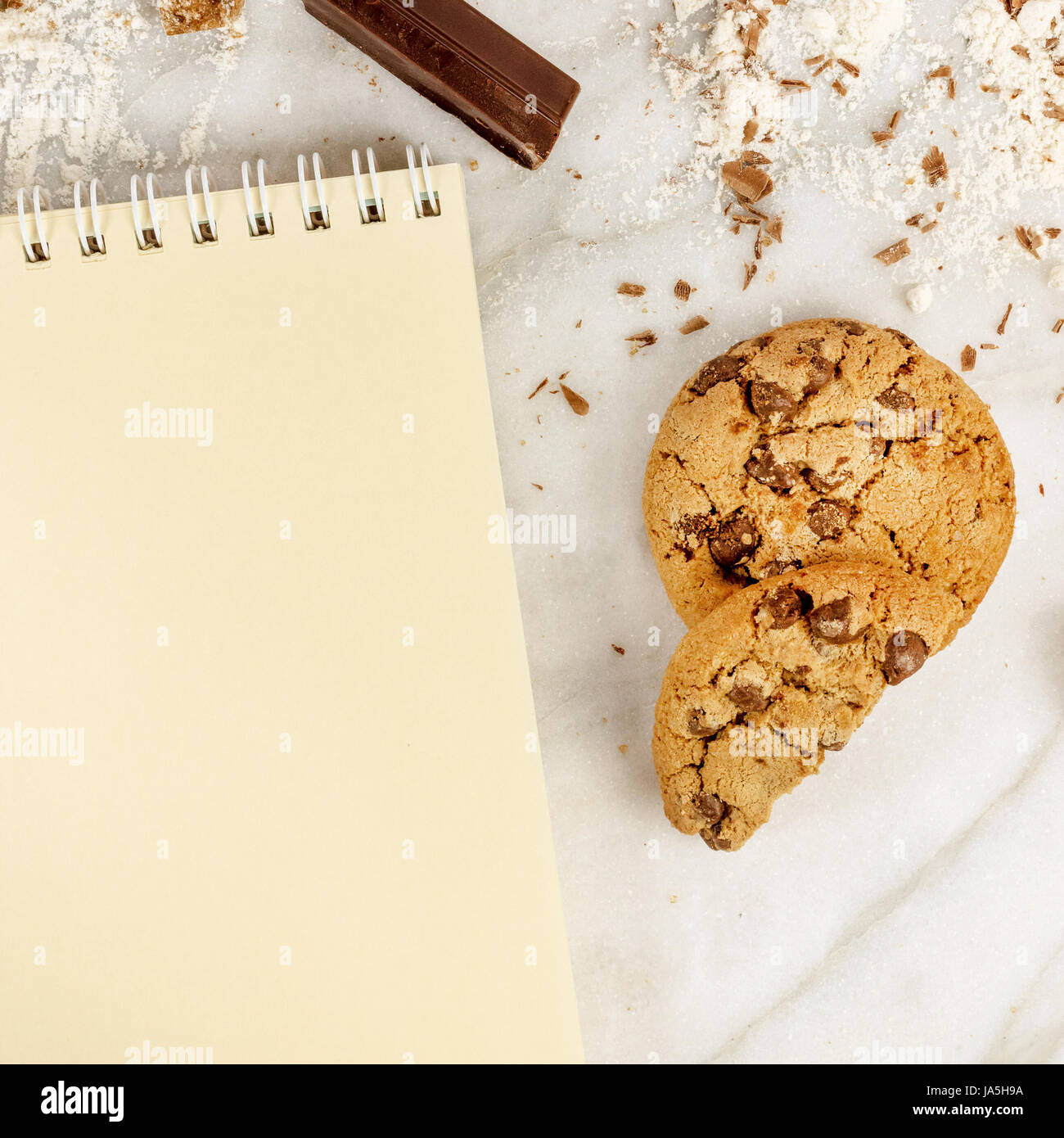 The process of making chocolate chips cookies. Overhead shot of biscuits with chocolate pieces, flour, and cane - Stock Image