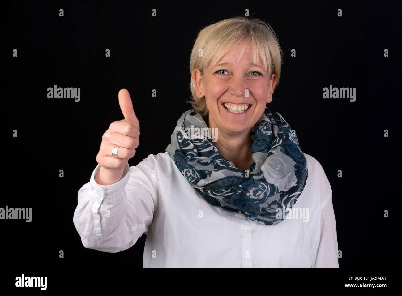 attractive blonde mature woman giving thumbs-up as positive sign
