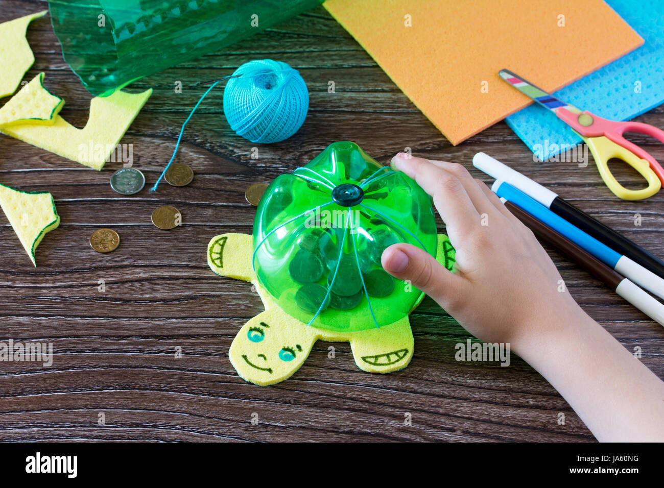 The Child Holds A Childrens Hand Craft From Plastic Bottle For Money Piggy Bank Handmade Project Of Creativity Handicrafts Crafts Fo