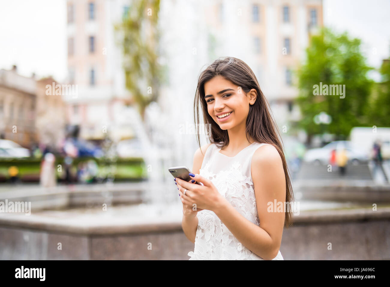 Young beauty woman writing message on cell phone in a street cafe. Looking down - Stock Image