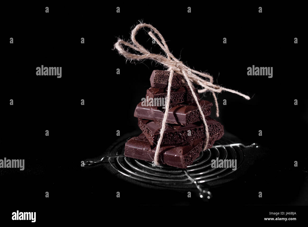 A stack of black pore chocolate tied with twine thread - Stock Image