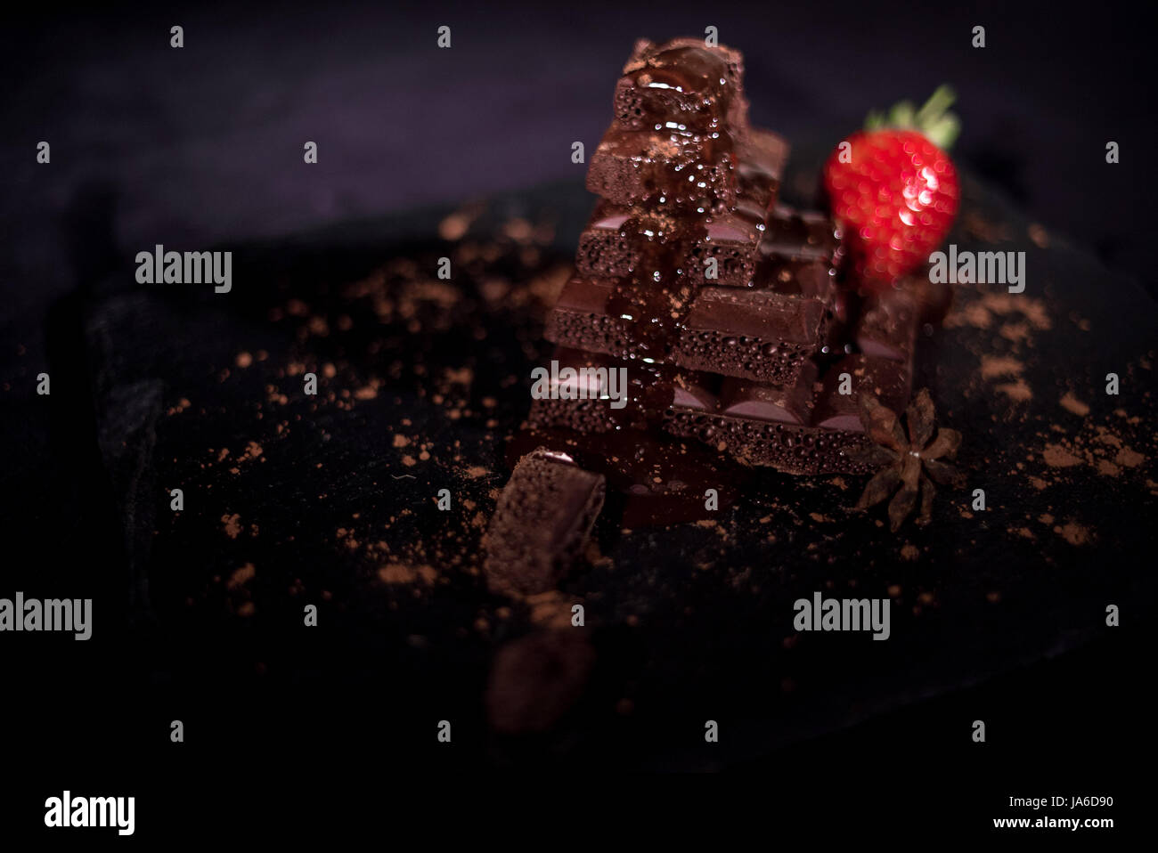 One red straberry on a dark  chocolate - Stock Image