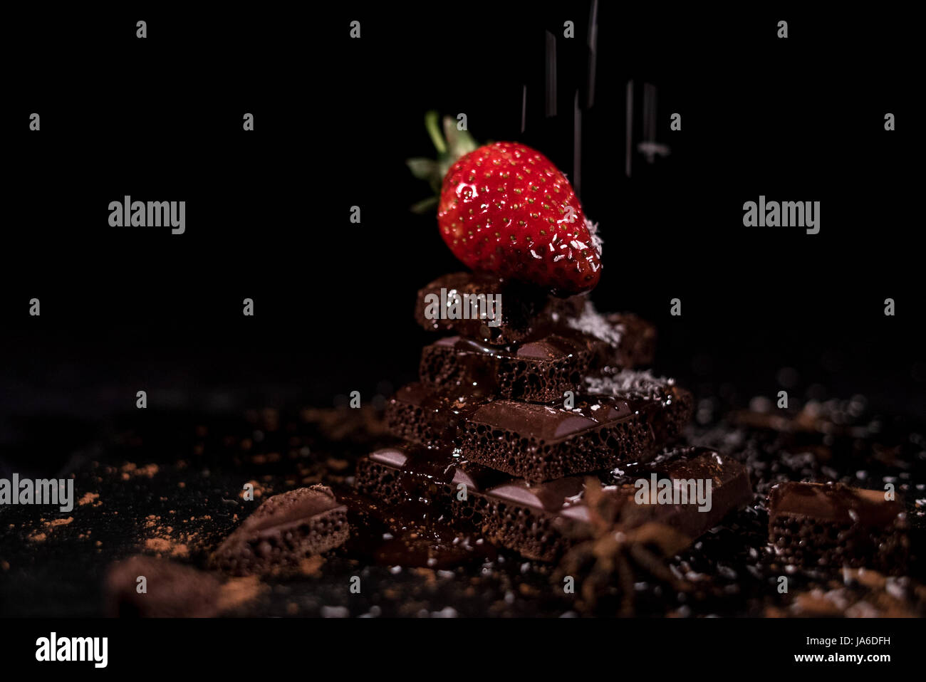 One red straberry on a dark  chocolate, crushed.Coconut chips - Stock Image