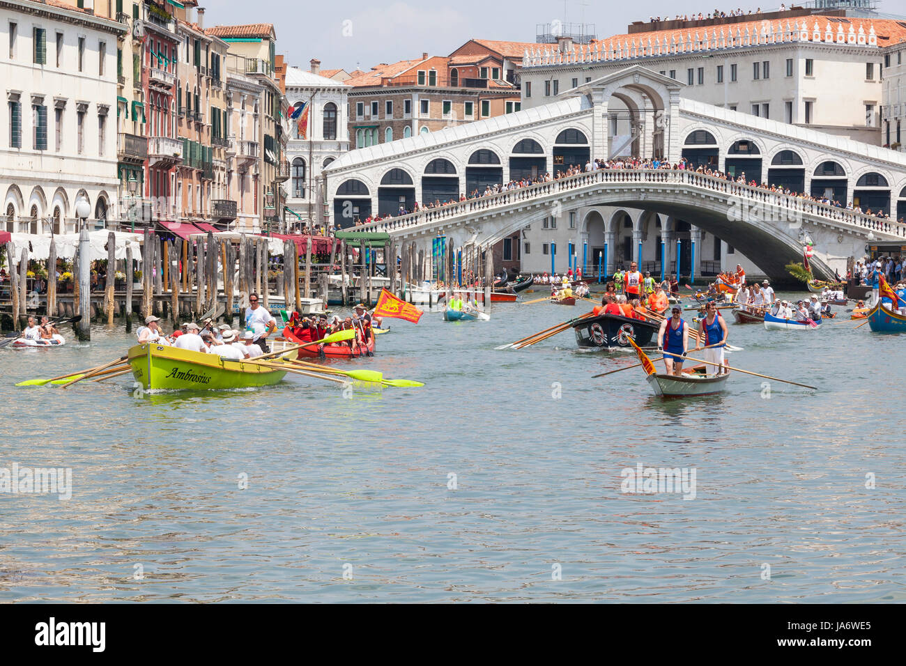 Venice, Veneto, Italy, 4th June 2017. Colorful assortment of traditional rowing boats passing under the Rialto Bridge - Stock Image