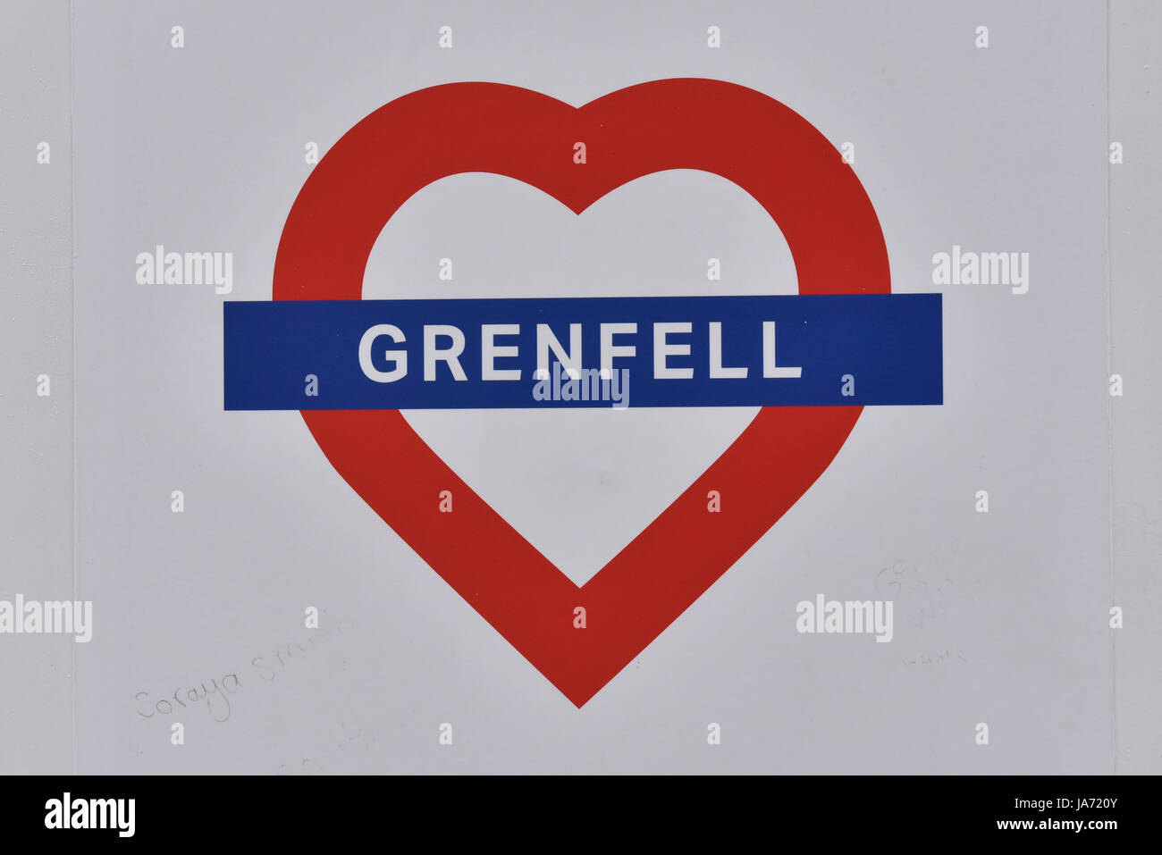 London, UK.  24 August 2017.  A heart logo affixed to the hoardings outside the burned out shell of Grenfell Tower - Stock Image