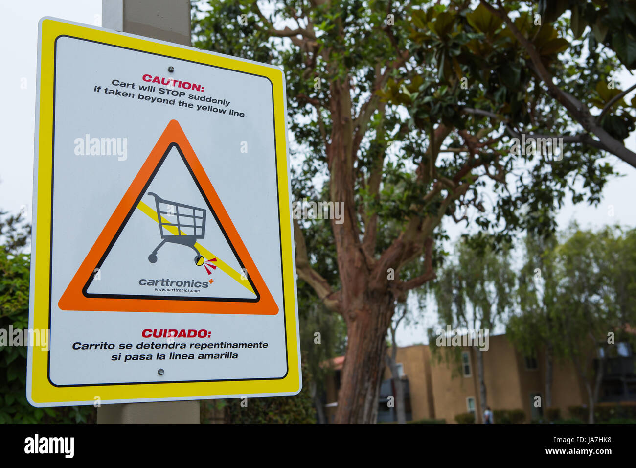 Caution carts will stop suddenly sign. Carttronics a developer of electronic systems used to stop the loss of shopping Stock Photo