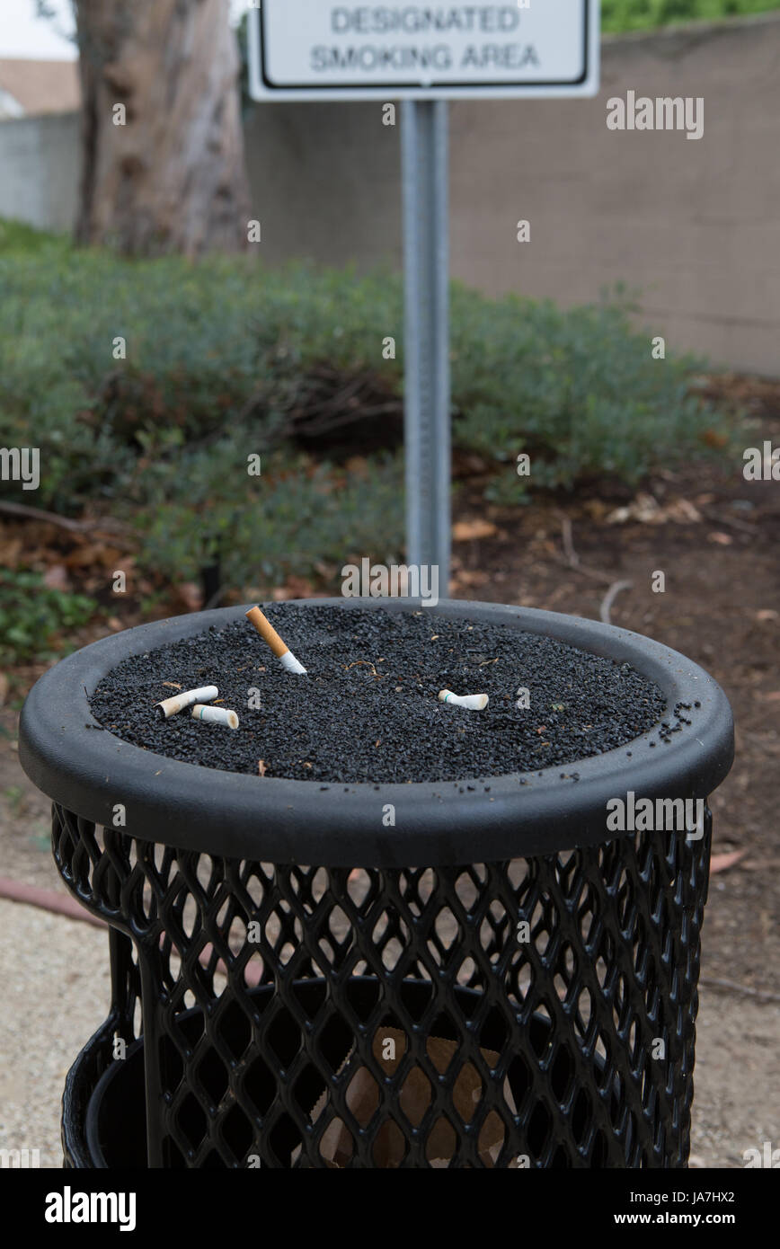 An ashtray for smokers and a designated smoking area sign outside a office building Stock Photo