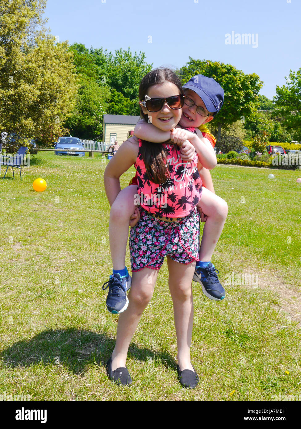 A young girl gives her younger brother a piggy back - Stock Image