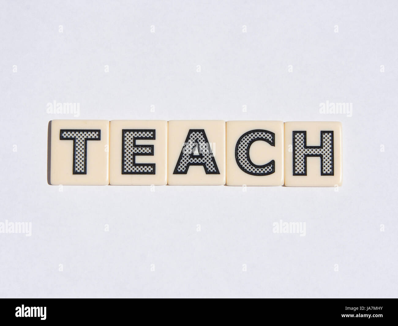 Letters on white tiles spelling out the word teach - Stock Image