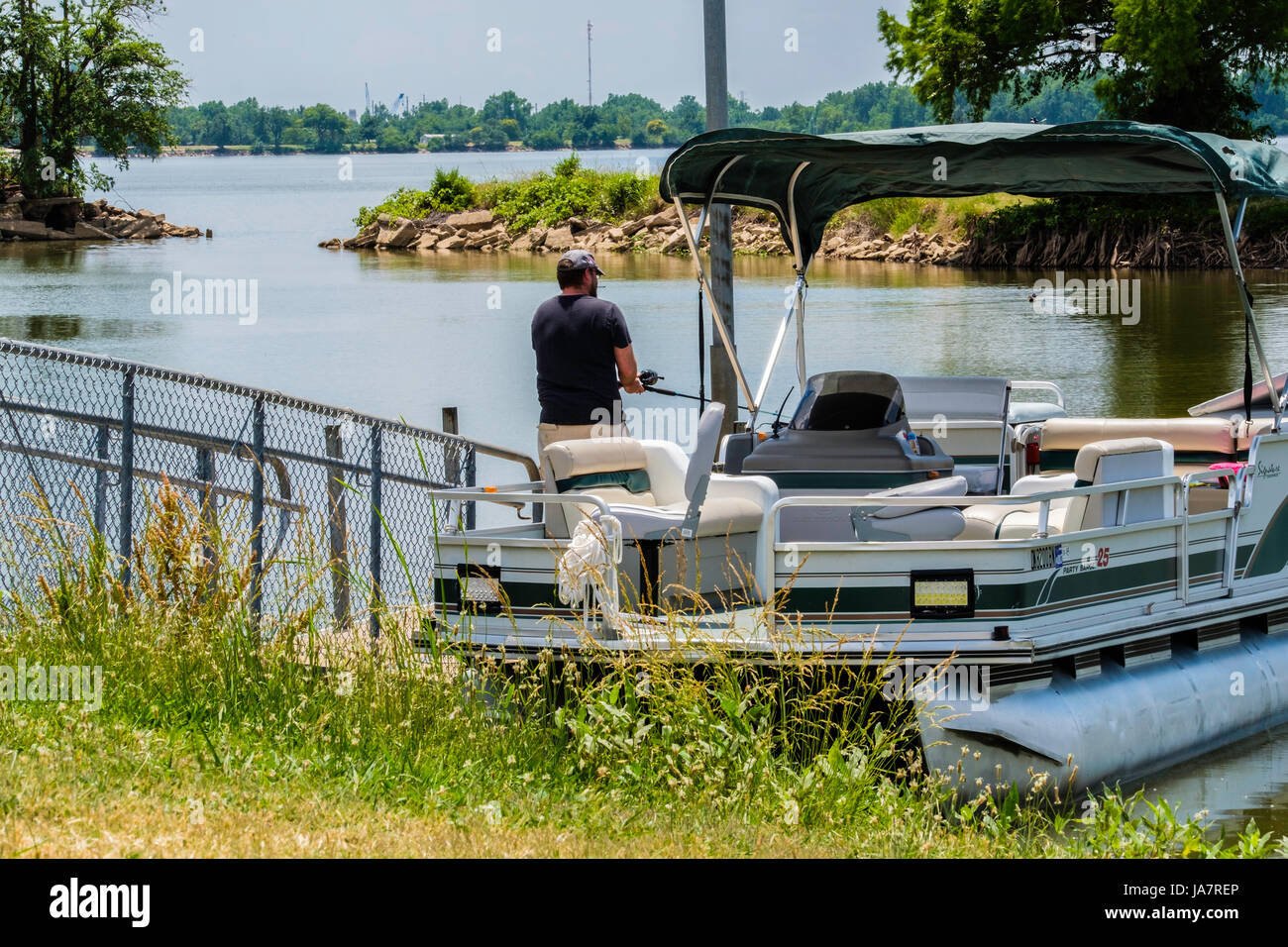 A Caucasian man in his 40s fishes from a pontoon boat on the North Canadian river near Oklahoma City, Oklahoma, - Stock Image