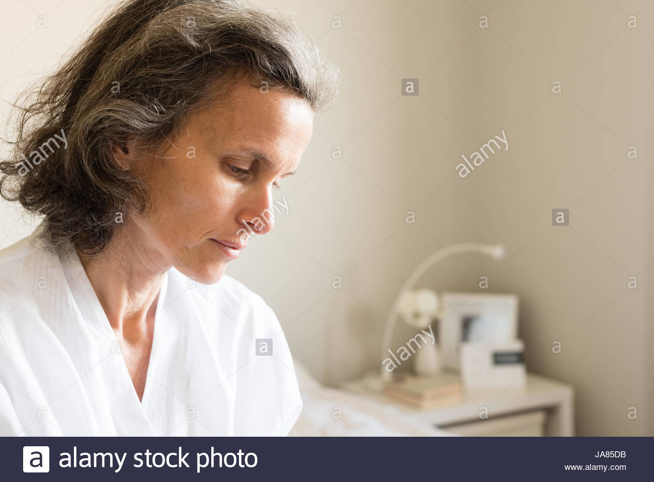 Profile view of middle aged woman with grey hair seated on bed in white robe (selective focus) - Stock Image