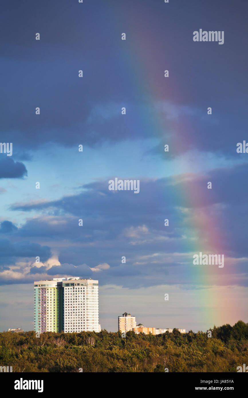 autumn rainbow under city park in dark blue sky - Stock Image