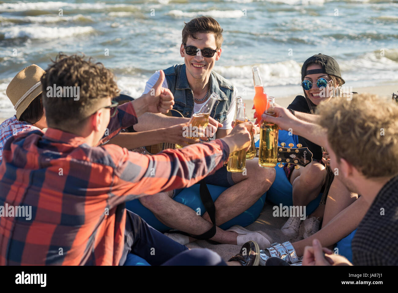 group of friends drindking on the beach party - Stock Image