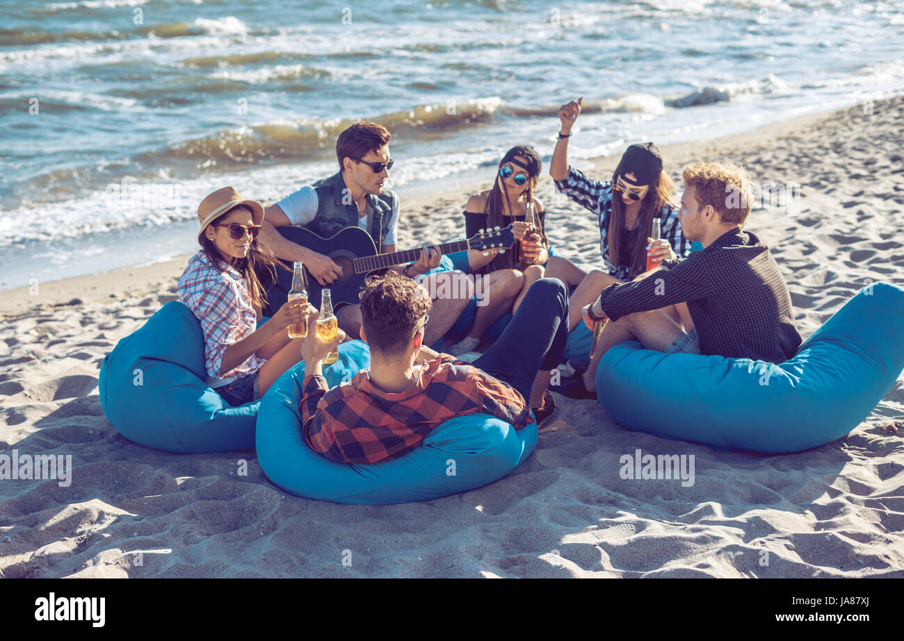 group of friends drinking on the beach party - Stock Image