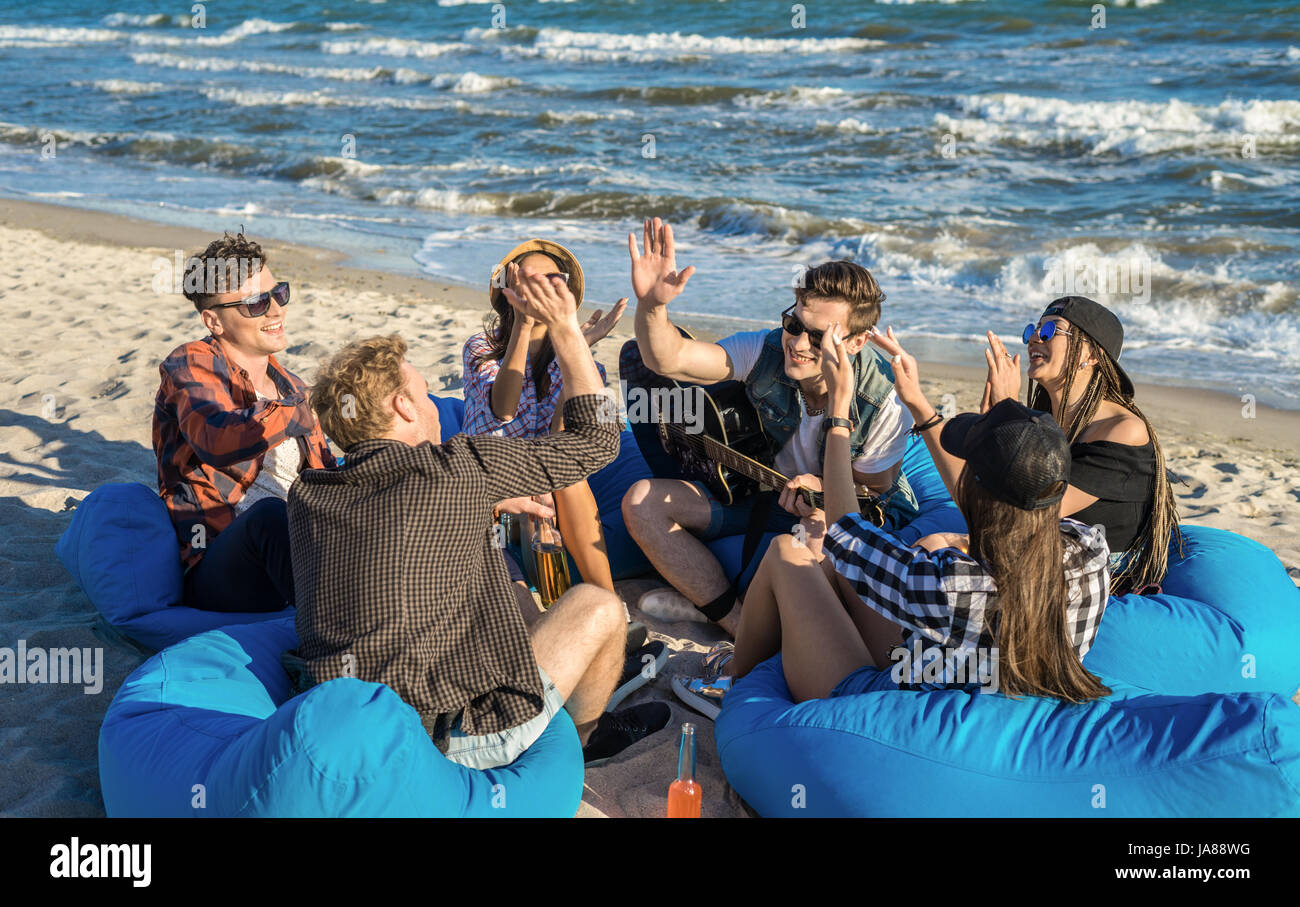 group of friends giving high five on beach sitting on bean bags - Stock Image