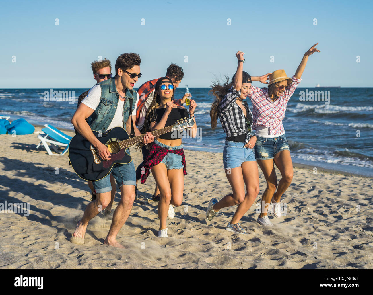 Party on the beach with guitar. Friends dancing together at the beach - Stock Image