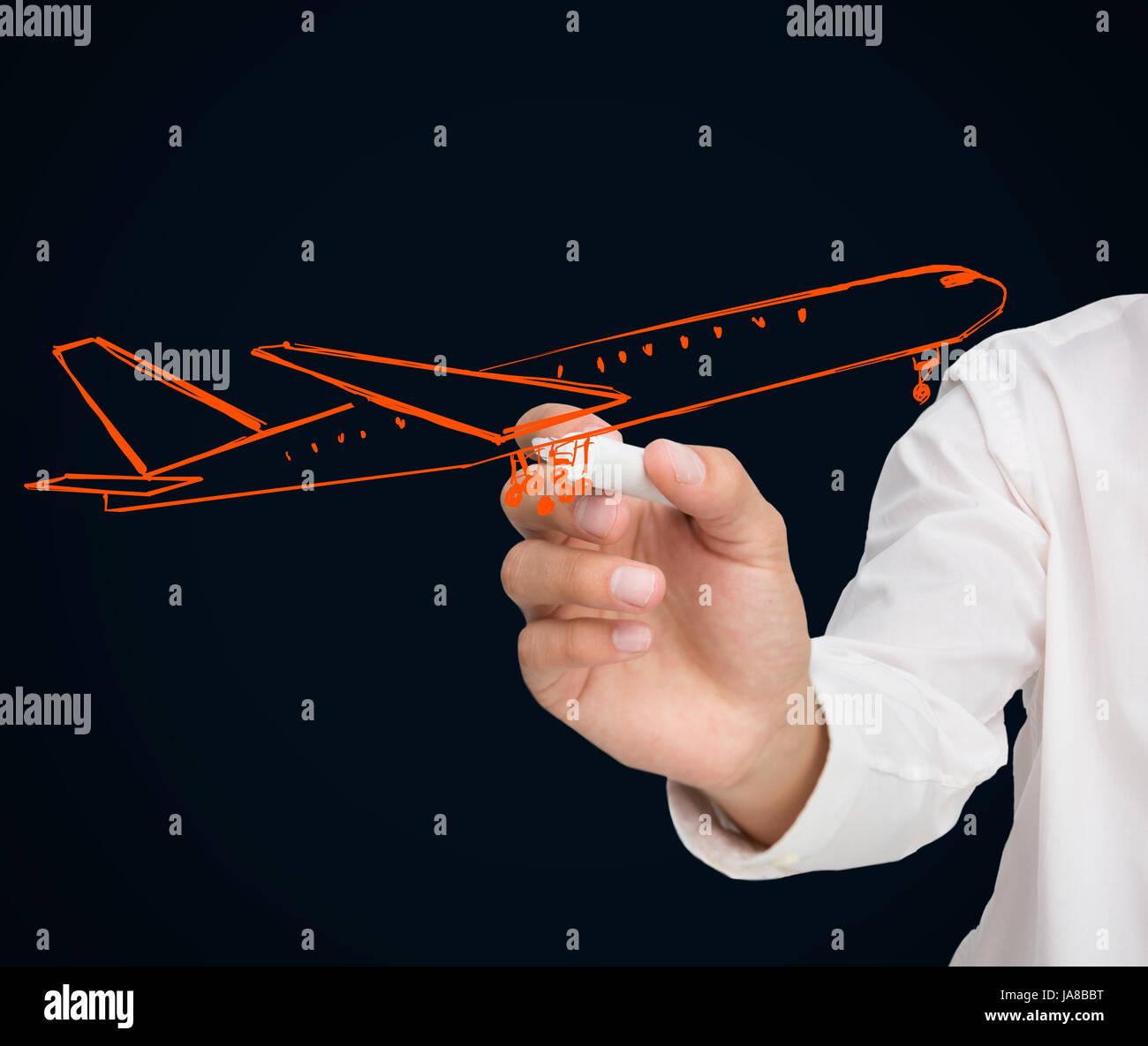 Buisnessman drawing orange airplane on black background - Stock Image