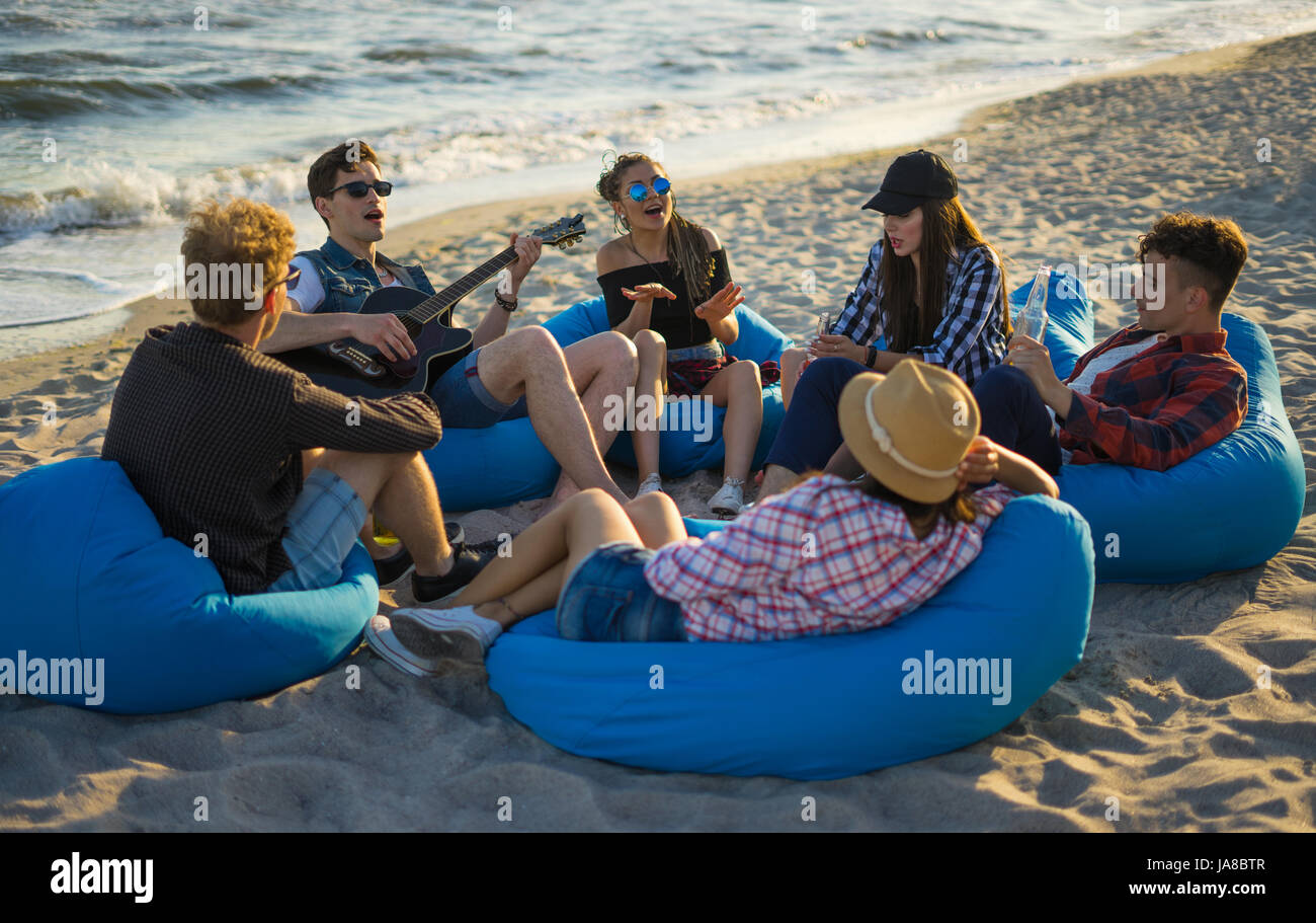 Friends singing guitar songs on the beach - Stock Image