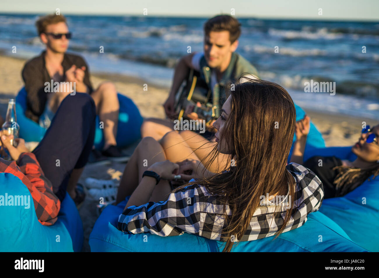 group of friends with guitar and alcohol on the beach party - Stock Image