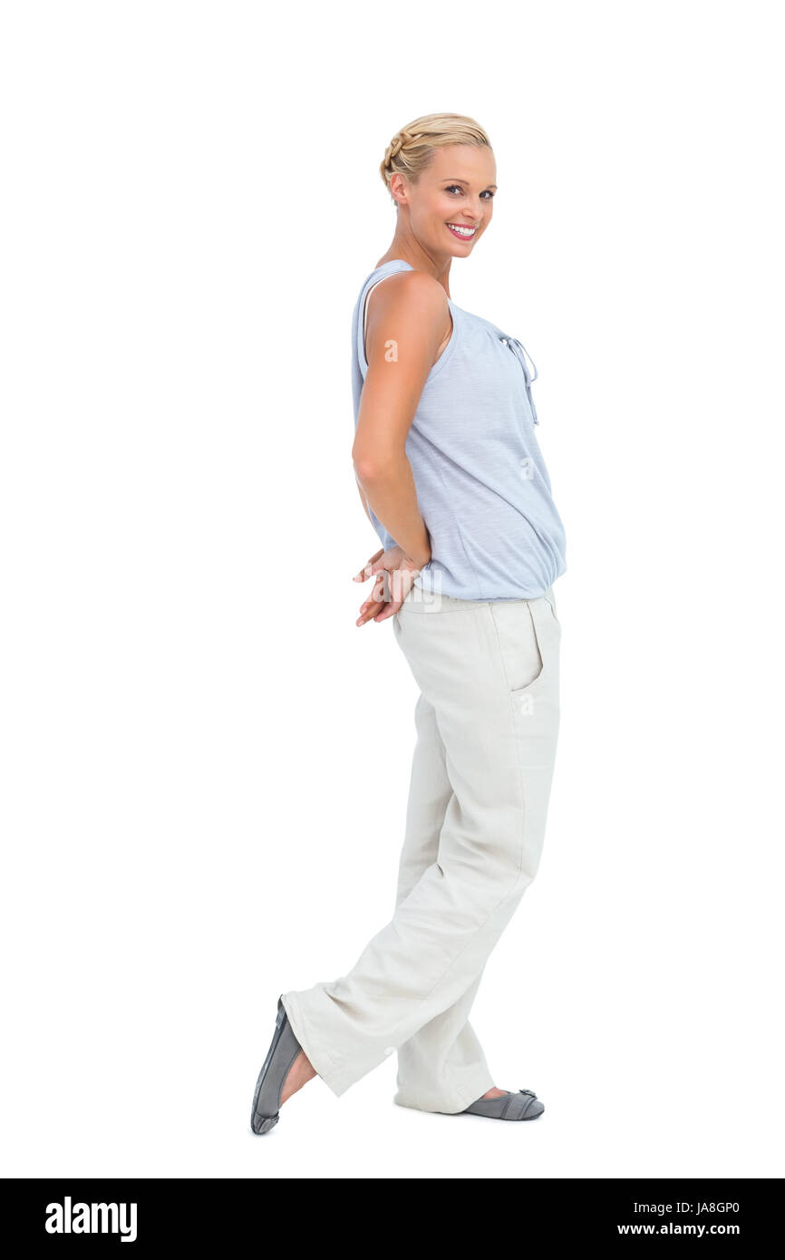Woman looking at camera with hands behind her back on white background - Stock Image
