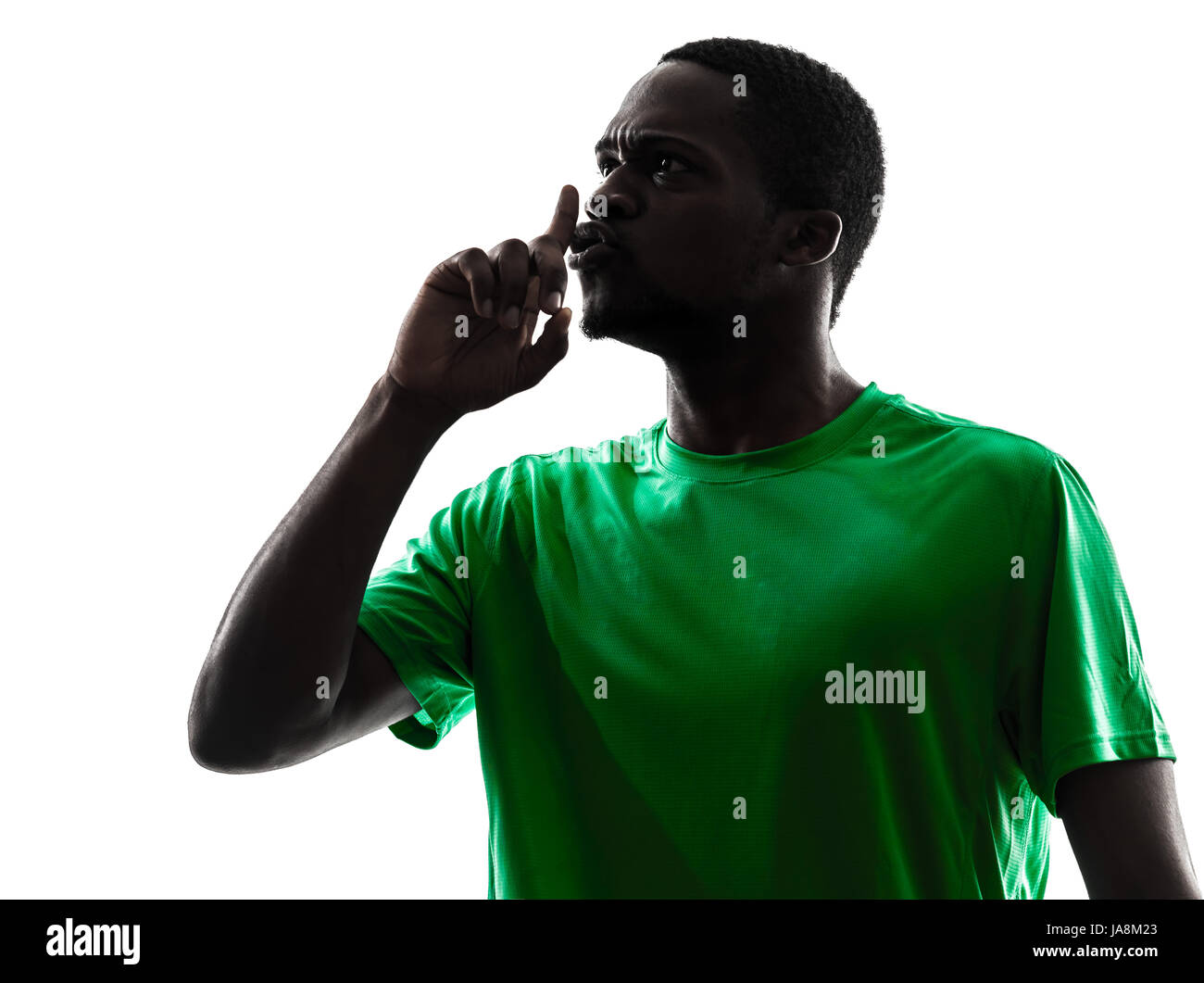 one african man soccer player hushing green jersey in silhouette  on white background - Stock Image