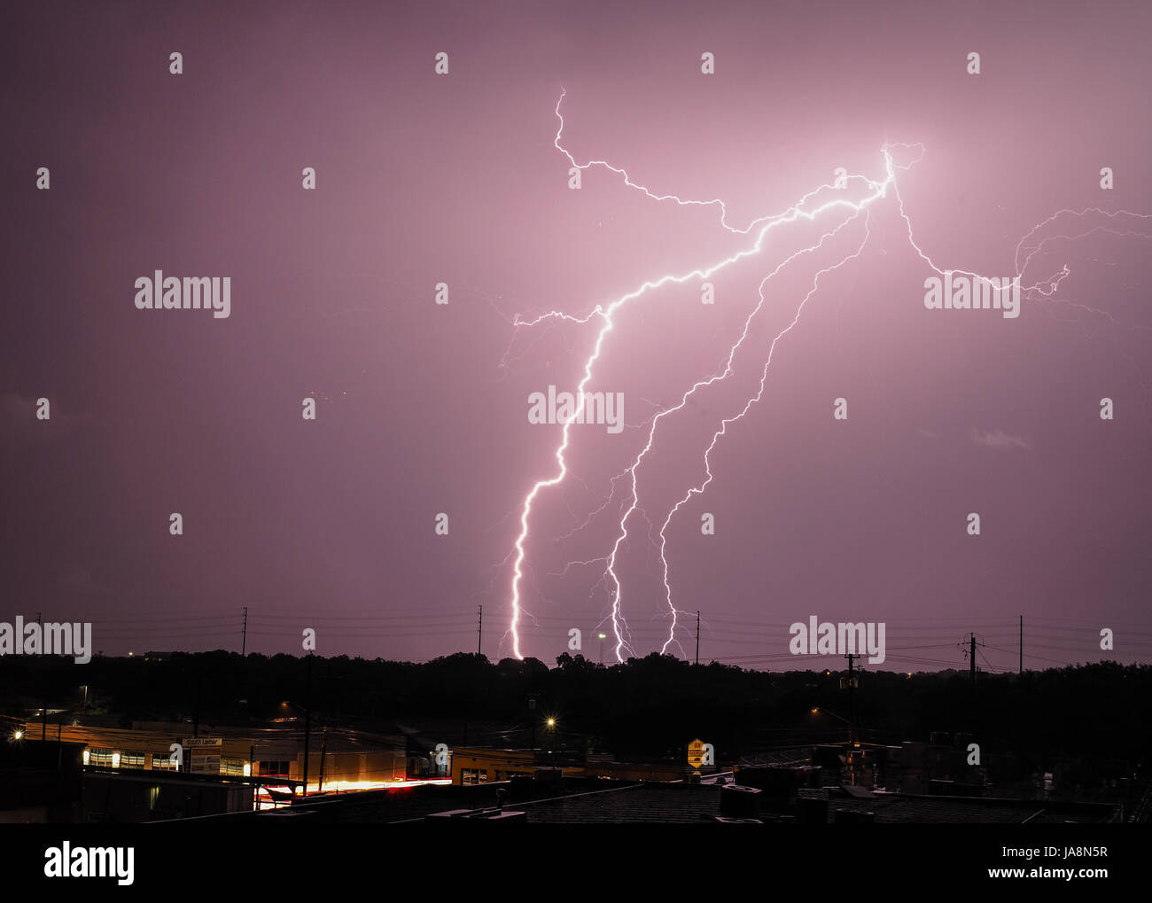 Multiple lightning bolts from a single source strike at night Stock Photo