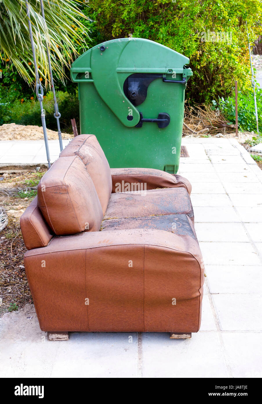 Old sofa near green trash can in the street . - Stock Image