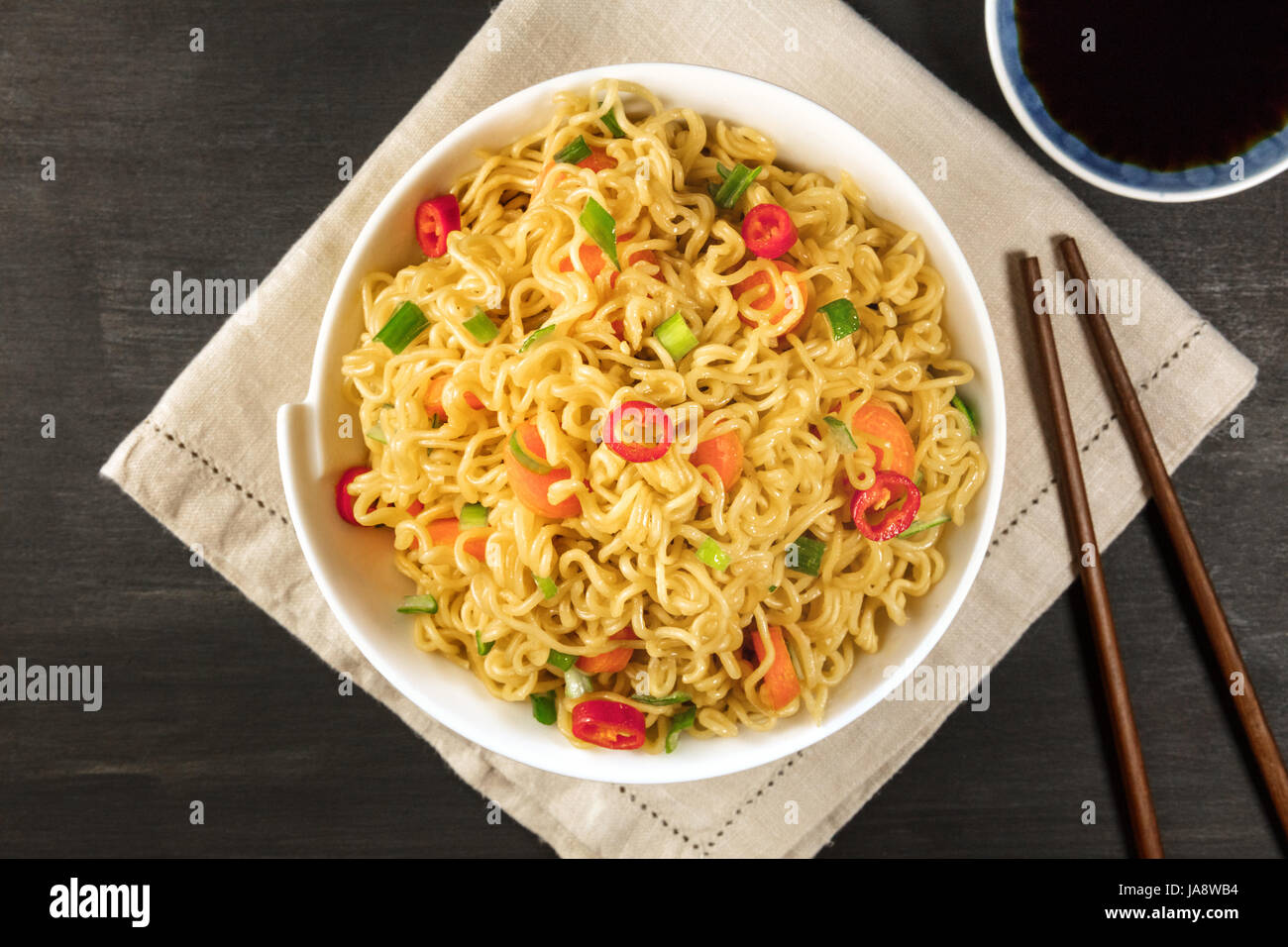 Instant noodles with vegetables, sauce, chopsticks, copy space - Stock Image