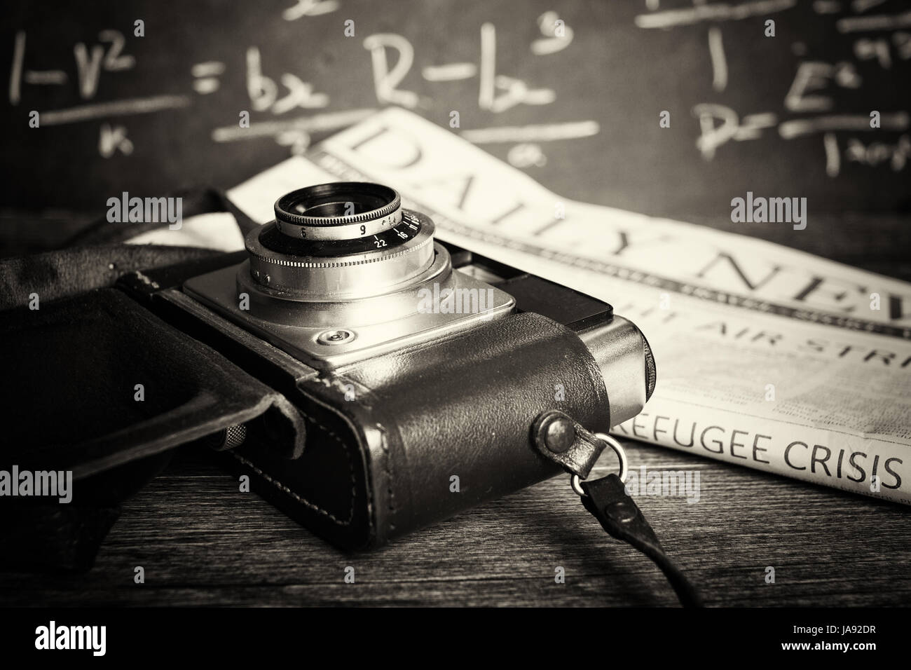 Old vintage retro camera with mocked up daily newspaper - Stock Image