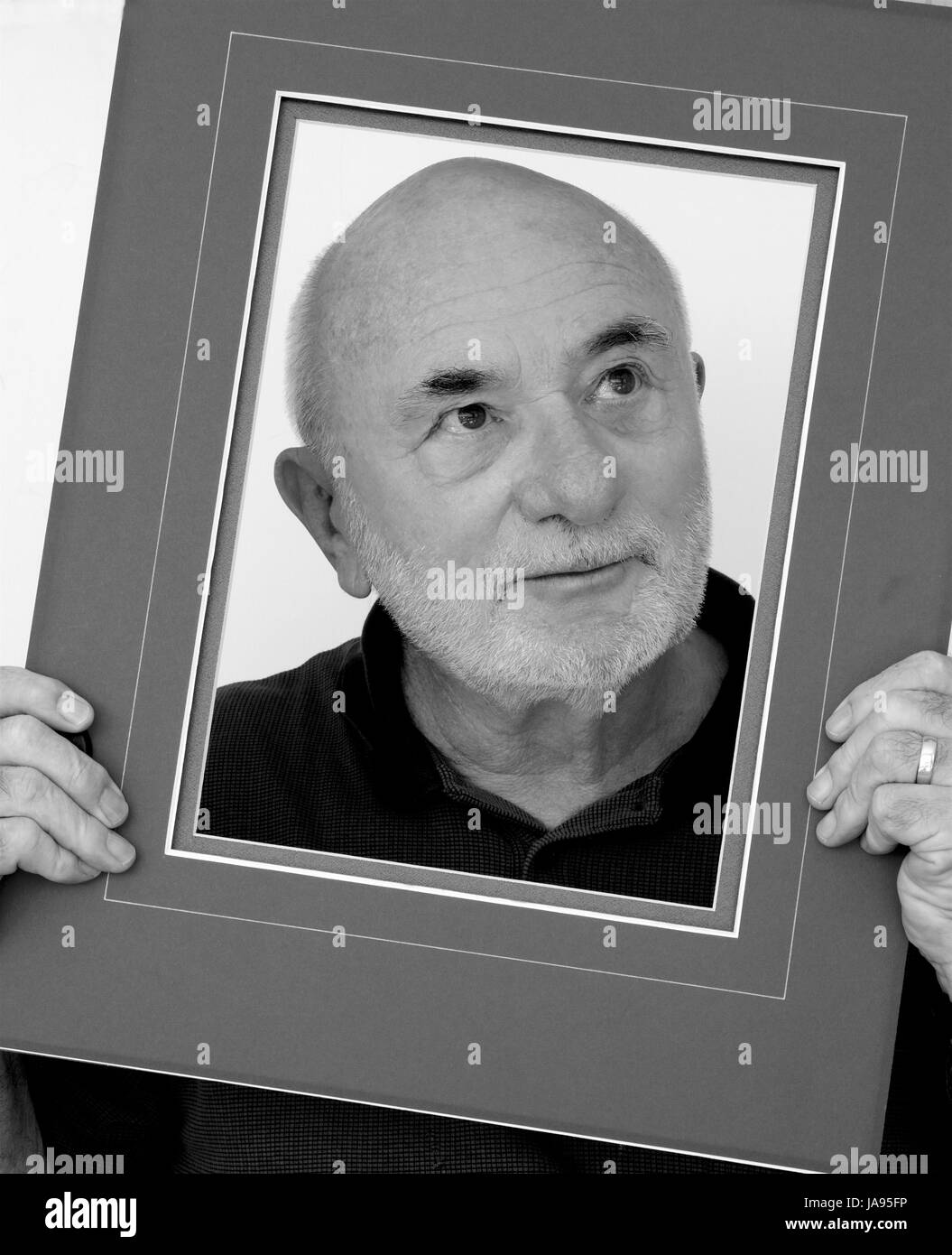 Old man in a picture frame in black and white. - Stock Image