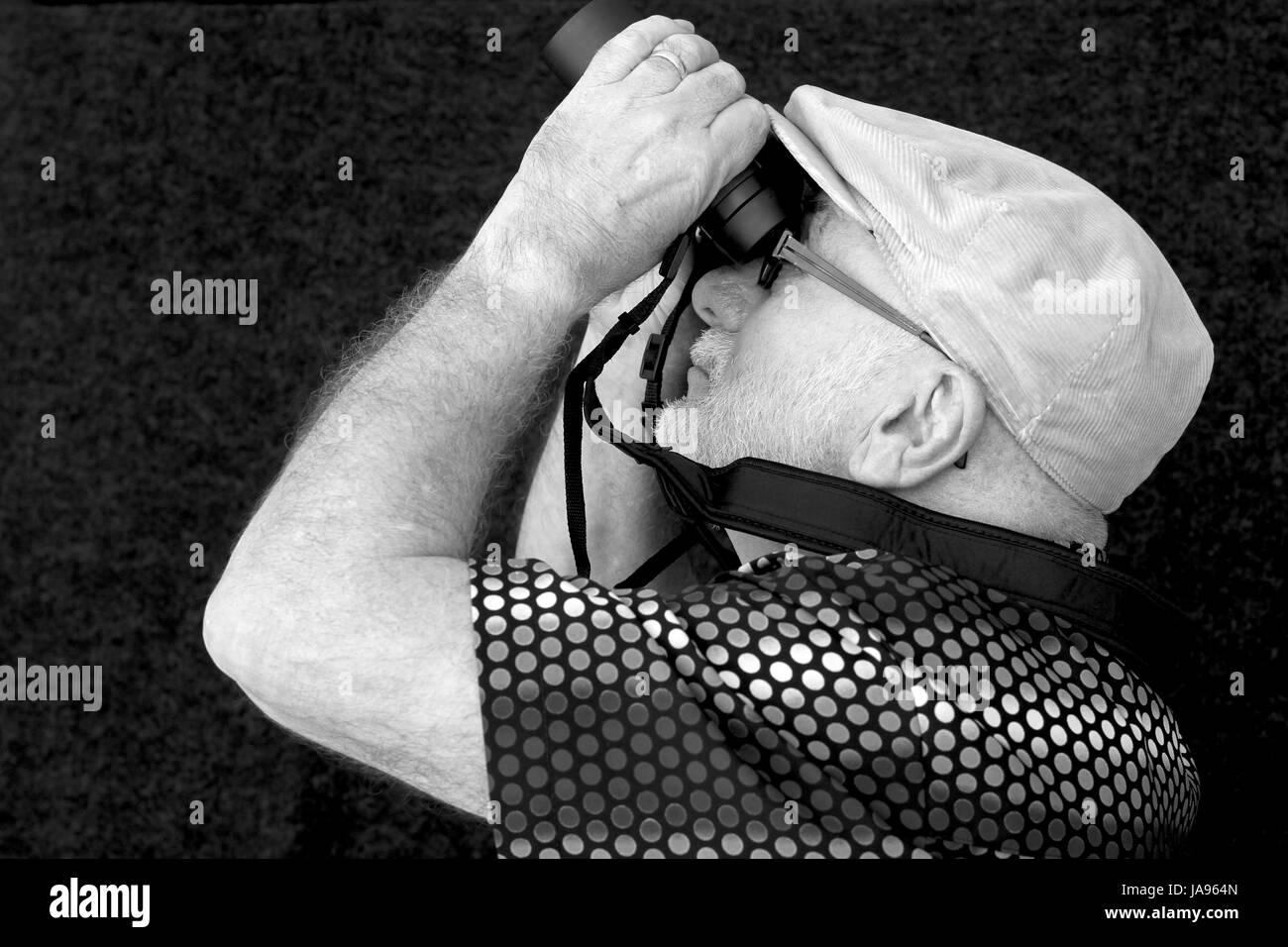Old man with binoculars. - Stock Image
