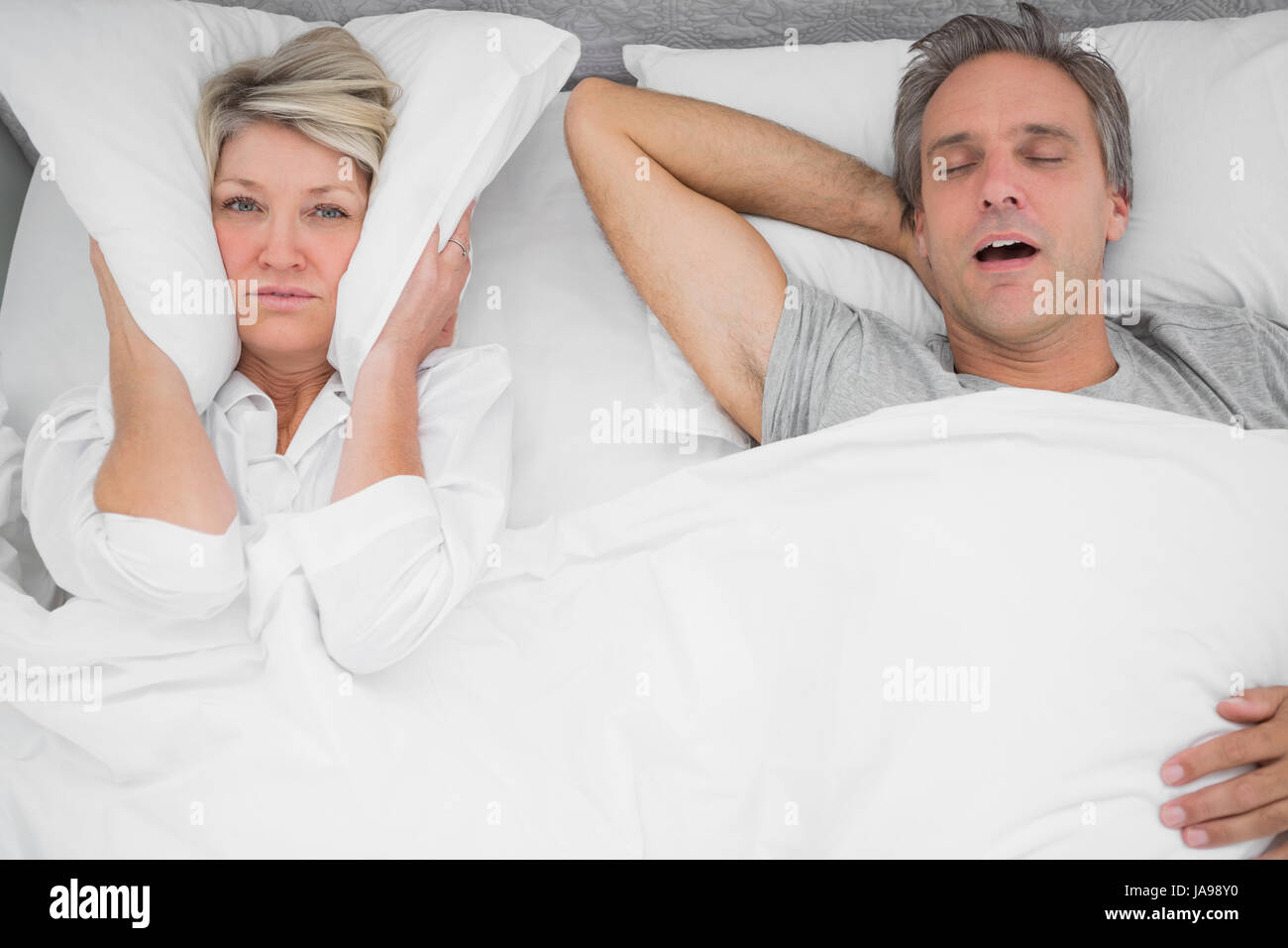 Man snoring loudly as partner blocks her ears at home in bedroom - Stock Image