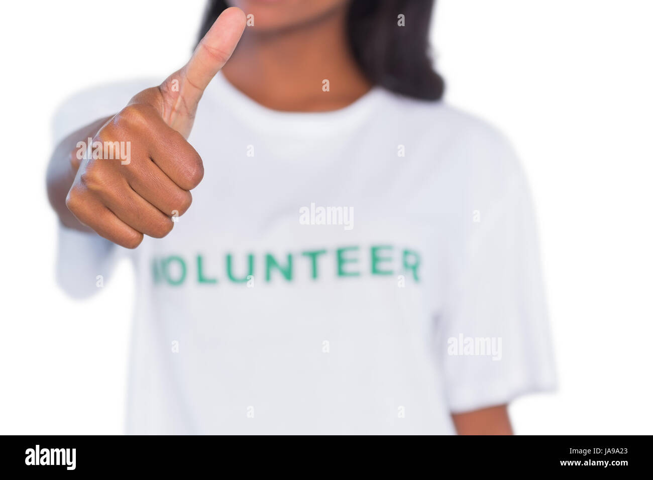 Woman wearing volunteer tshirt and giving thumb up on white background - Stock Image