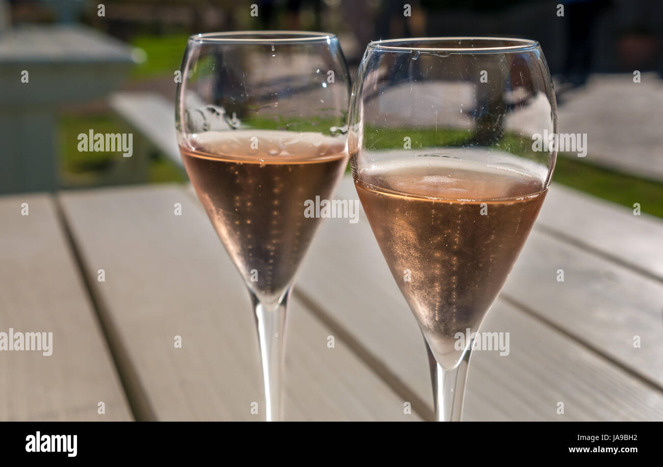 Close up pair of full wine glasses with pink Rosé wine on sunny outdoors deck table, Haute Cabriere winery, - Stock Image