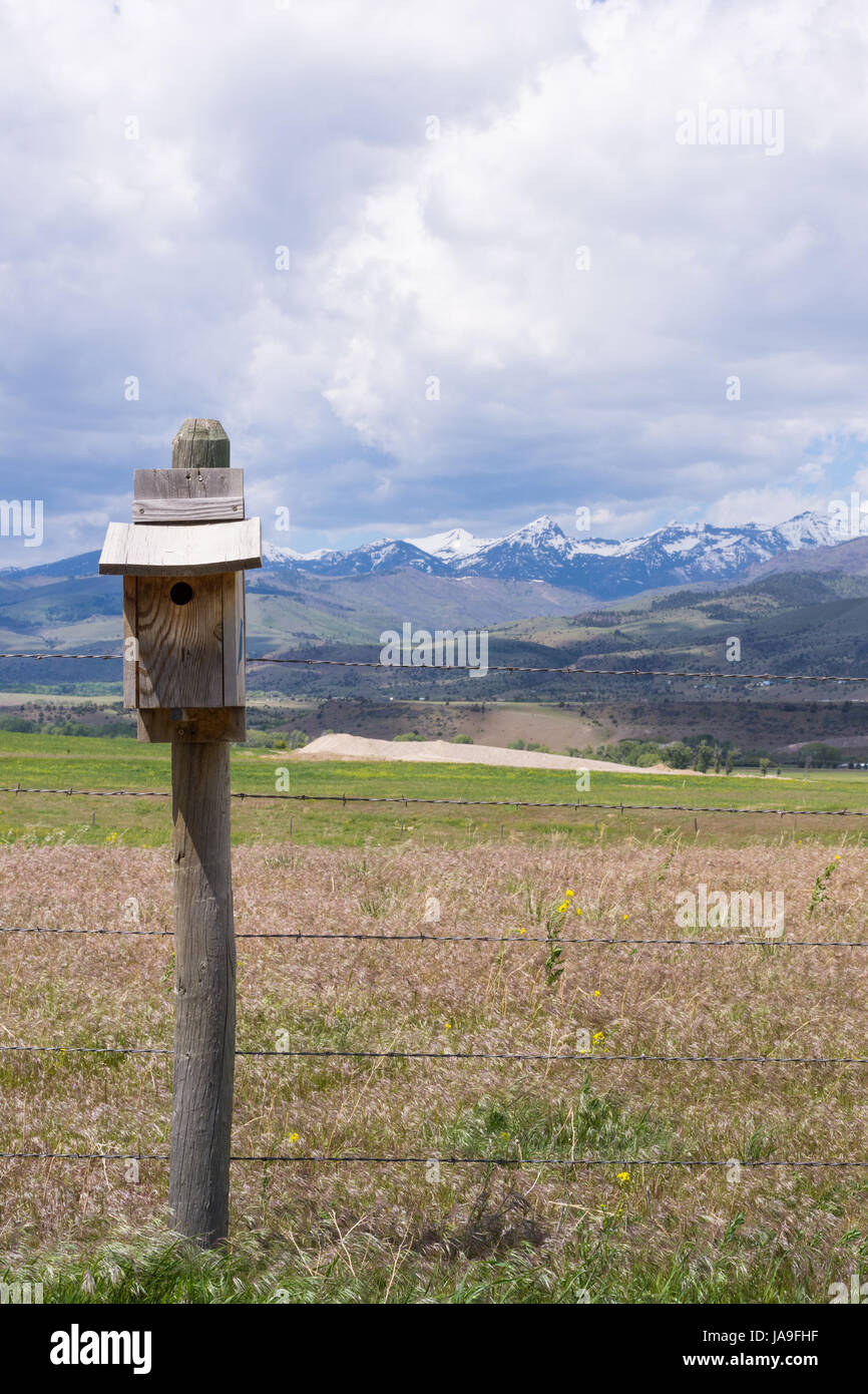 Close up of weathered bluebird house on a fence post with rugged, snow capped mountains and foothills in the background. - Stock Image