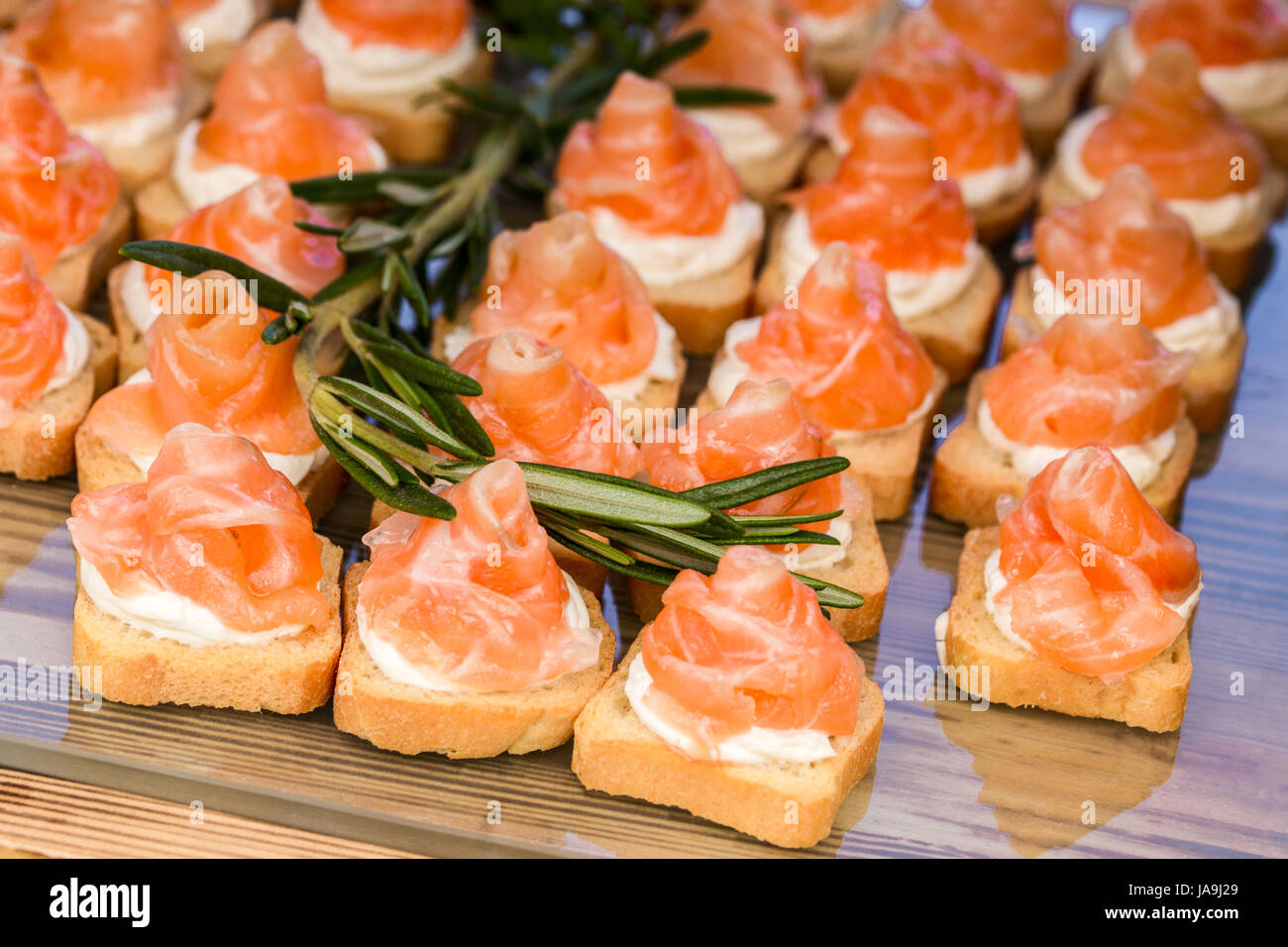 mini canapes with smoked salmon and rosemary sprig . - Stock Image