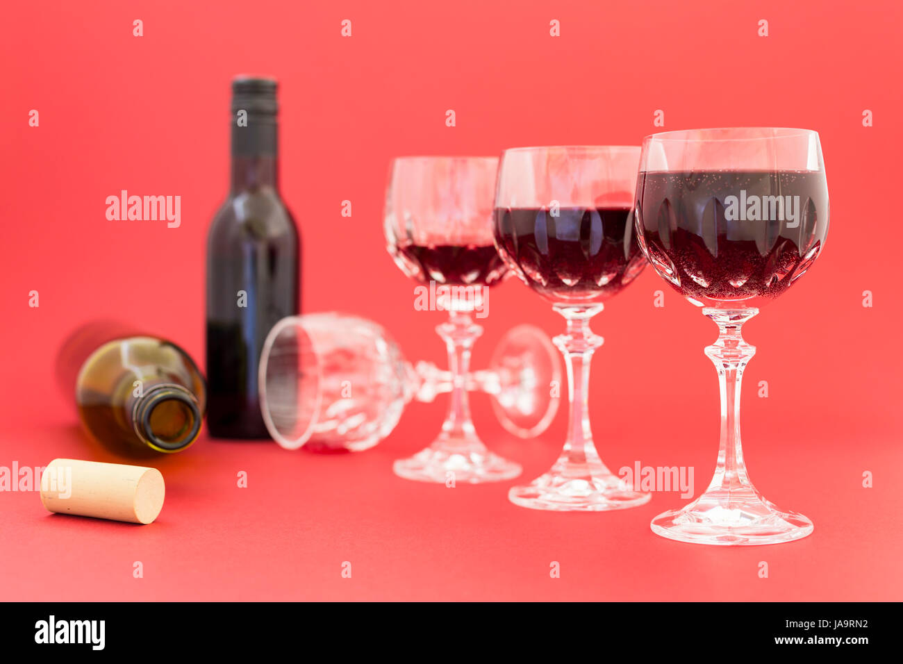 Concept of alcohol consumption, alcoholism and abuse with a line of beautiful crystal glasses filled with red wine, - Stock Image