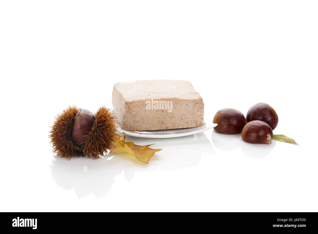 Chestnut puree with raw chestnuts isolated on white background. - Stock Image