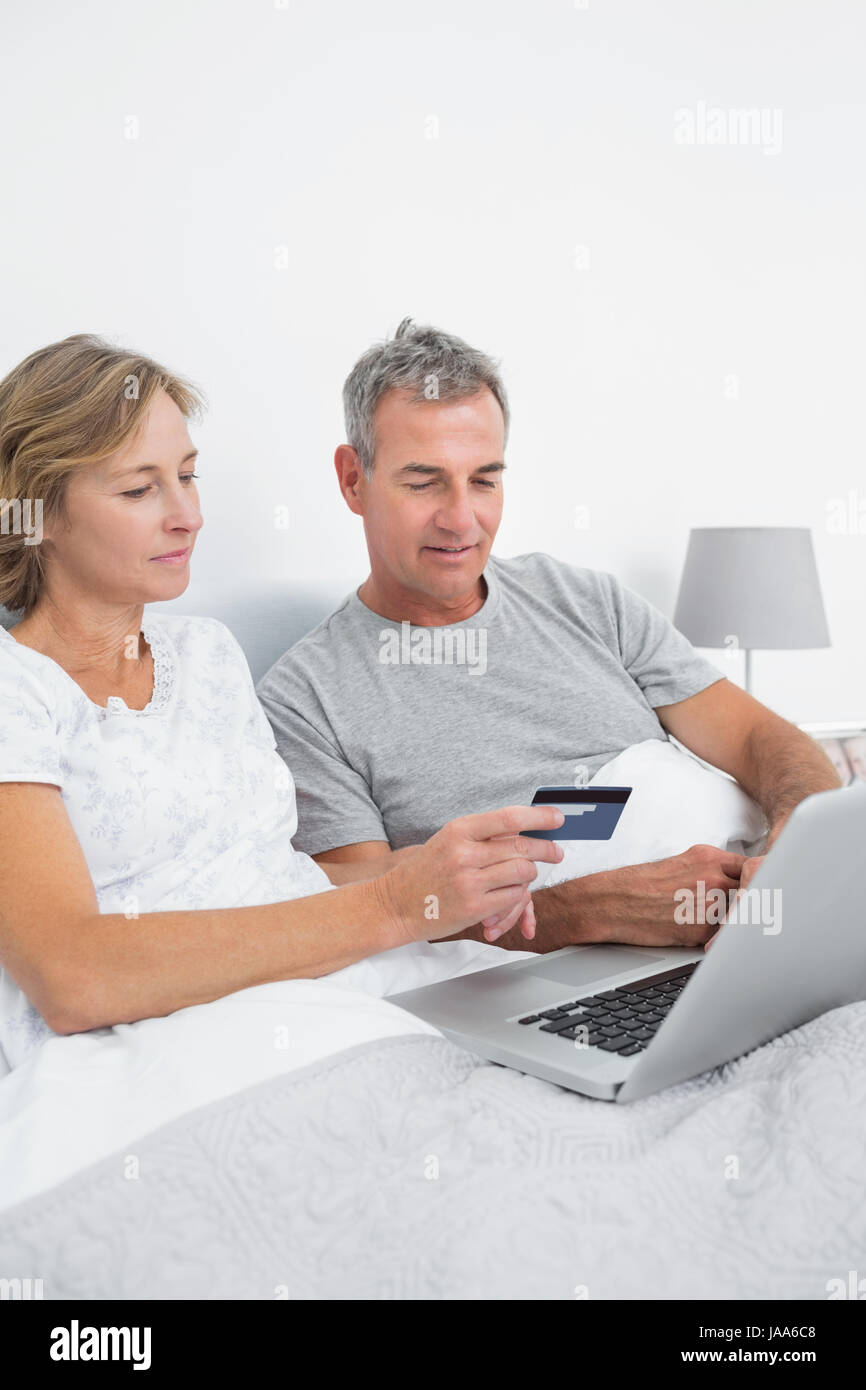 cheerful couple using their laptop to buy online at home in bedroom rh alamy com online at home typing jobs online at home work