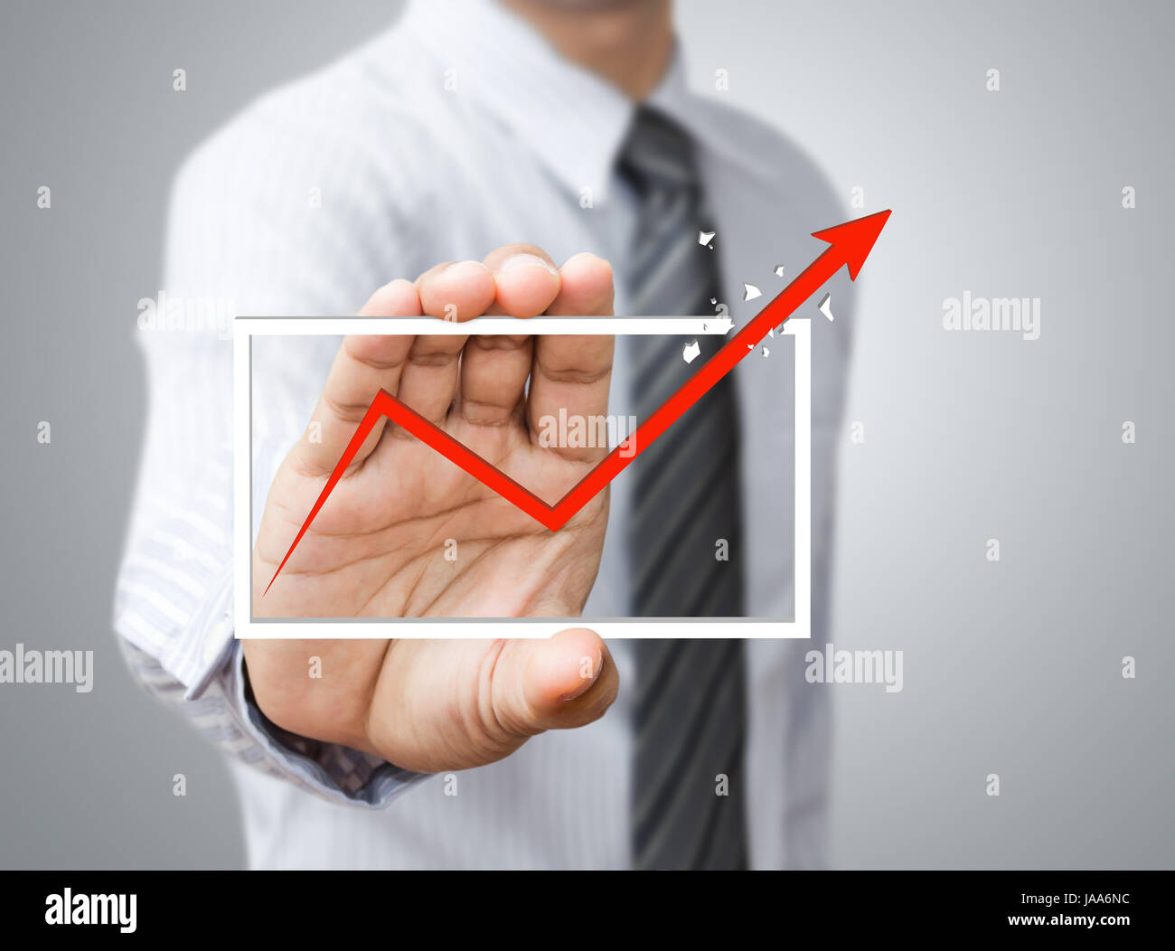 Hand holding a rising arrow, representing business growth. - Stock Image