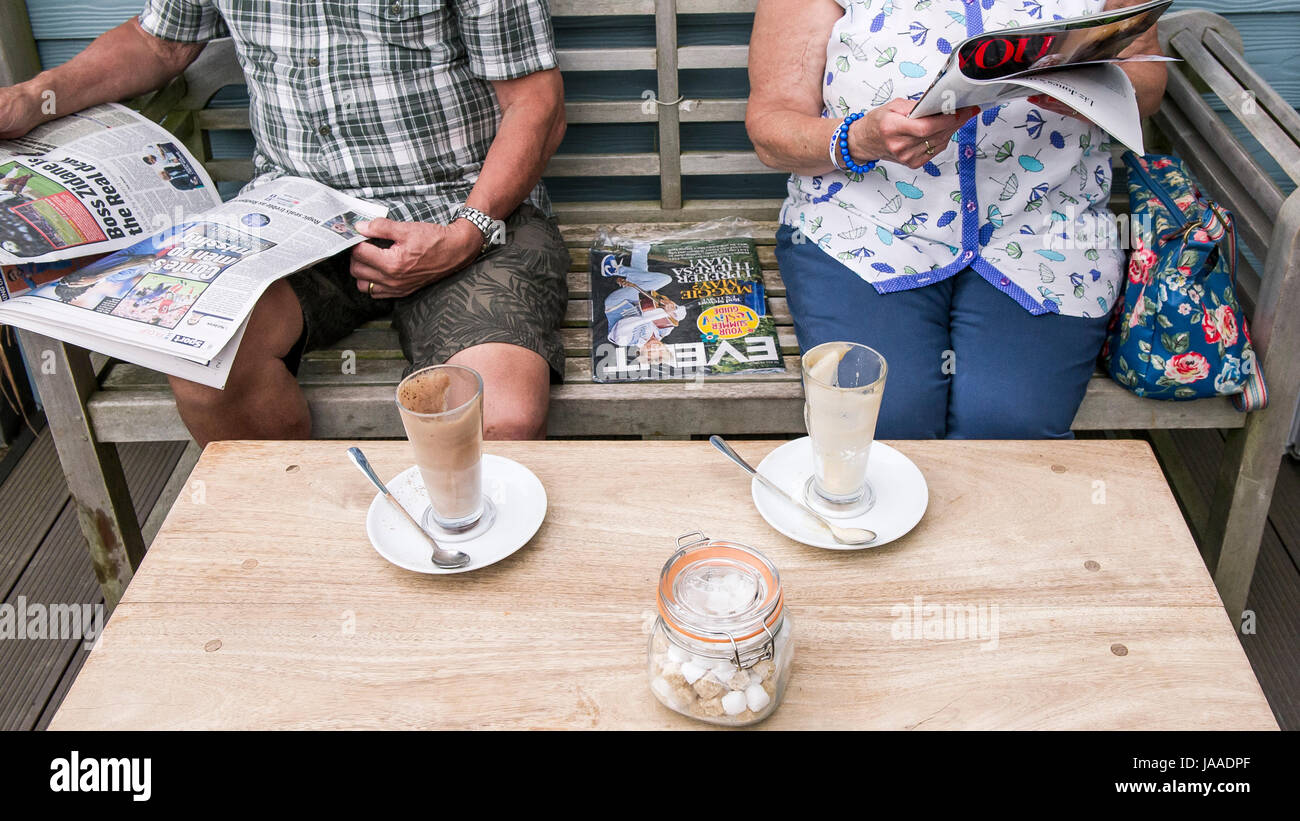 Customers relaxing in an outside area of a cafe. - Stock Image