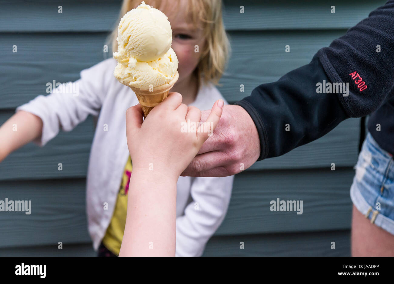 An adult giving an ice cream cone to a child. - Stock Image